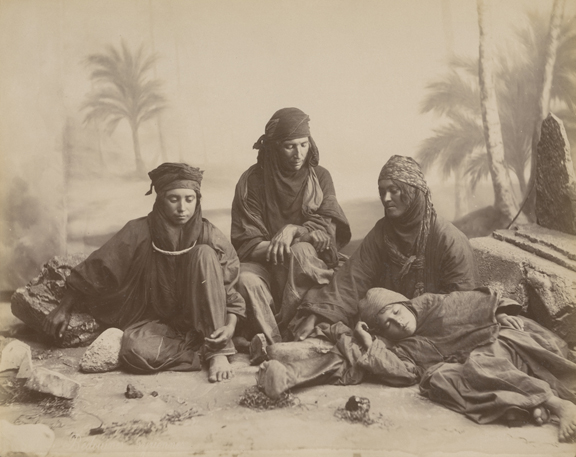 Studio set up to resemble a desert. Three people sit a younger boy lying on the sand.