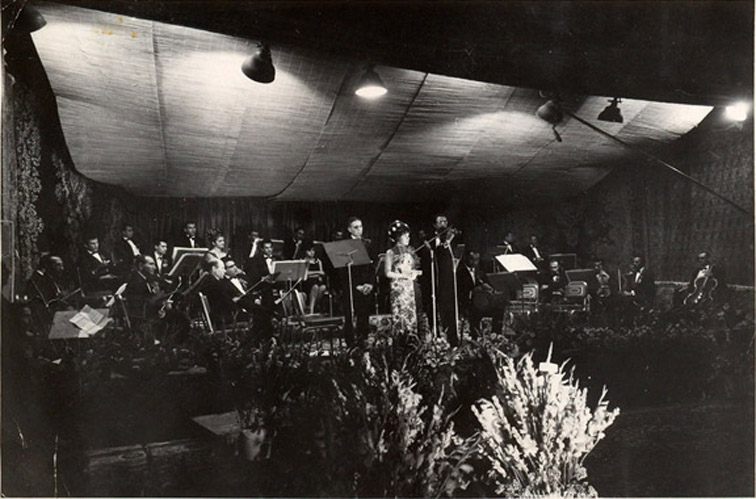 An orchestra and female singer in a recording studio.