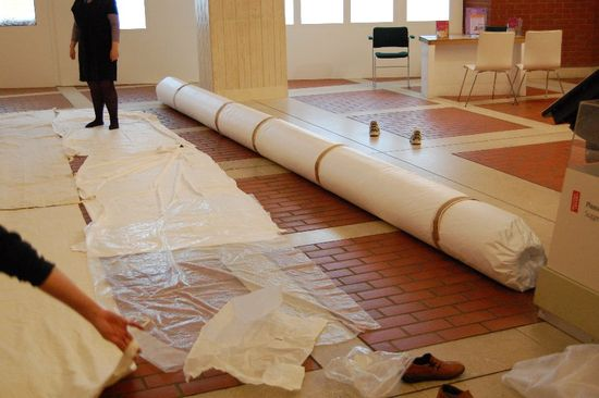 This image shows a long tube covered in a white material called Tyvek, lying on a brick and white tile floor. This is the inner role used to support the tapestry once taken down off the wall. The floor has sheets of white protective material laid out in rows parallel to the tube, which will be wrapped around the tapestry once on the tube for safe transport and handling.