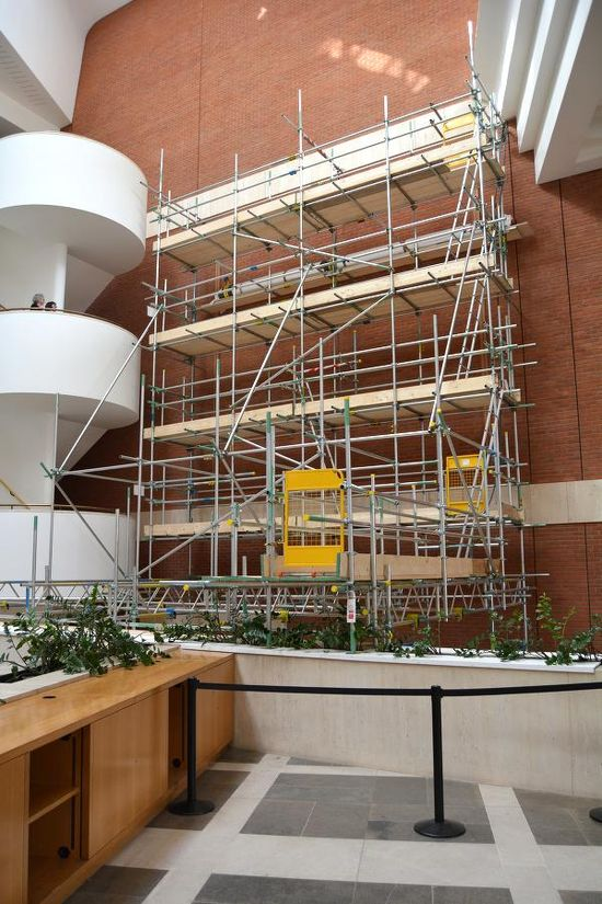 A view of a five-level scaffolding installed in front of a red brick wall where the tapestry once was.