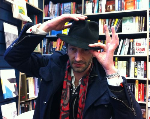 Photograph of Antoine Laurain, with hat, in front of a bookshelf
