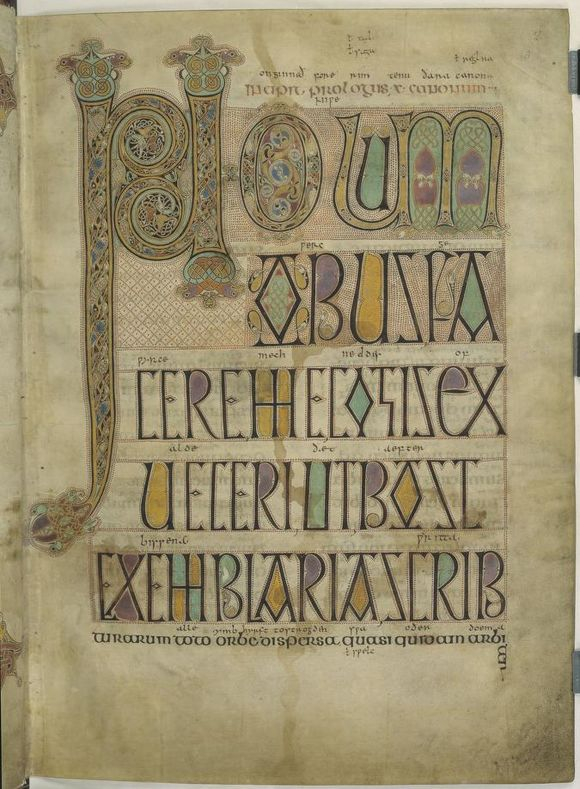 A parchment page of illuminated text. The initial, in the upper left corner of the page, is the largest letter on the page, and extends down the left margin almost to the bottom of the page. It is decorated with swirling motifs, the heads of leopard-like animals, and interlocking birds. The main colours used for decoration are purple, light green, yellow, blue and black. There are two more letters on the first row, which are smaller than the initial but decorated in the same style. The rest of the text on the page, consisting of another five lines, is simpler and written in capitals in black ink. Some of the enclosed areas inside letters, such as A and B, are filled in with yellow, green and purple pigment. All these letters are surrounded by an outline of small red dots. A line of smaller, undecorated, red text runs along the top of each line, and an even smaller line of black text runs along the top of this