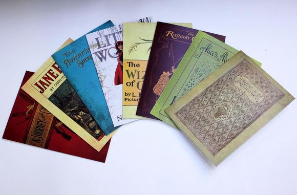 An array of eight brightly coloured greetings cards with book cover designs overlap in a fan shape. They lie on a light grey background.