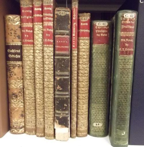 Nine books in glod-tooled leather bindings on a shelf