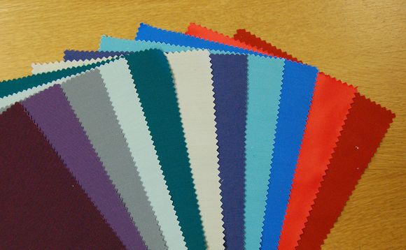 Eleven rectangular swatches of fabric in a variety of bright fabrics lie on a wooden tabletop.