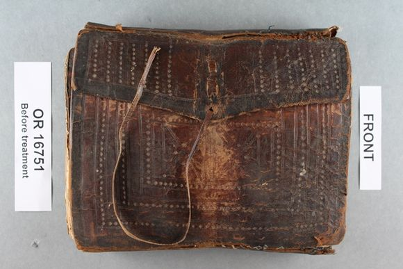 A book in a rectangular dark brown leather wrapping lies on a grey background. The picture is sideways, so that the head edge of the book is on the right-hand side. The wrapping is decorated with concentric rectangles of dots and lines imprinted onto the leather. A triangular leather flap folds over the front of the book from the spine edge, which is at the top of the photo. A leather thong is threaded through the point of the triangle. The leather is faded and is splitting at the spine edge.