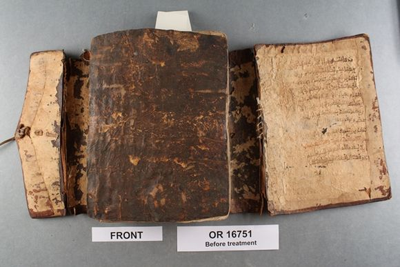 The unbound textblock lies in the middle of the open wrapper, with a dark brown leather board on top of it. The leather of the underside of the wrapper is much paler leather of a light orange-pink colour. There is an old repair on the right-hand side of the wrapper, where a tear has been repaired with white thread.