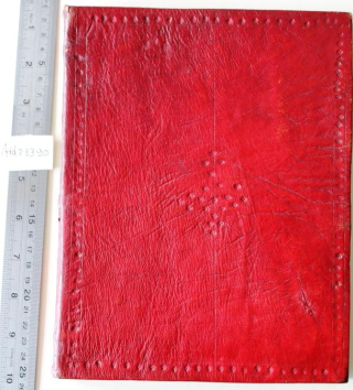 The front board of a book bound in red leather. The leather is creased and scratched. It is decorated with a border of lines and small five-petalled flowers. There is a double vertical line down the centre of the board. In the centre of the board a diamond shape has been created from five-petalled flowers.