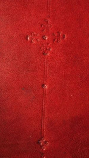 A detail of a section of board decoration, stamped onto red leather. A double line runs vertically down the leather. At the top of the line is a diamond motif consisting of four shamrock shapes with a five-petalled flower in the centre. In the middle of the line is a single five-petalled flower. At the bottom of the line is a diamond motif consisting of four five-petalled flowers with a single five-petalled flower just beneath it.