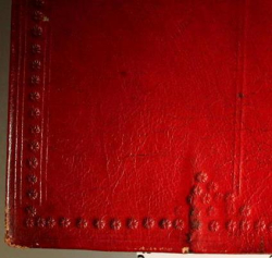 A detail of the decoration of the lower left corner of the back board of a book. It is covered in red leather, onto which the decoration is stamped. The decoration consists of a border of lines and small five-petalled flowers. In the right hand side of the photo is a double vertical line coming down to meet the border. At the bottom of the line, above the border, is a triangle consisting of four five-petalled flowers.