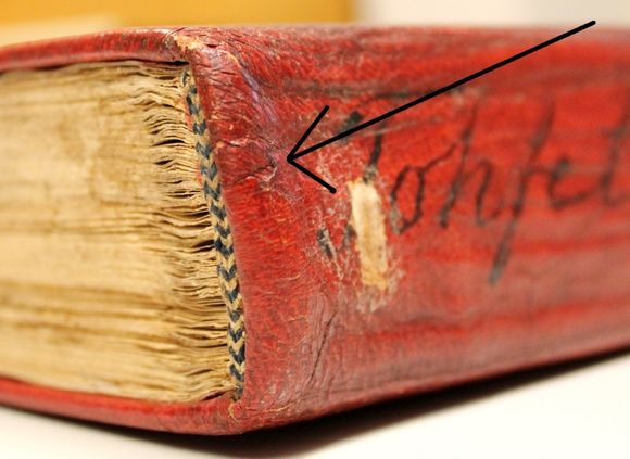 The area at the top of the spine of the same book. A black arrow shows a bump running beneath the leather at the spine of the spine. This is where the overlapping leather from the left board has been folded in over that of the right board to form a headcap.