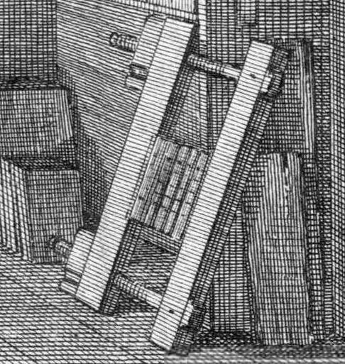 Books are stacked in a wooden press which is leaning against a wall.