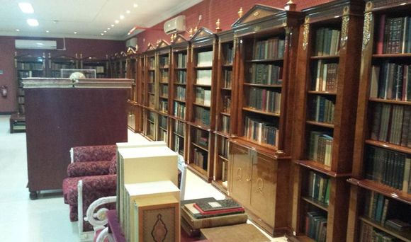 The walls of the Library are lined with books on wooden shelves, the walls are maroon in colour, and there is seating in front of the shelves.
