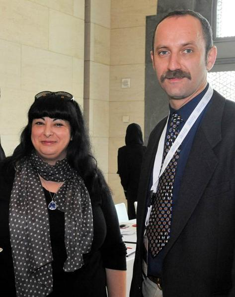 A woman and man pose for the camera. The woman is wearing black with a polka dot scarf, and the man is in a suit jacket with a tie that has a dotted pattern.