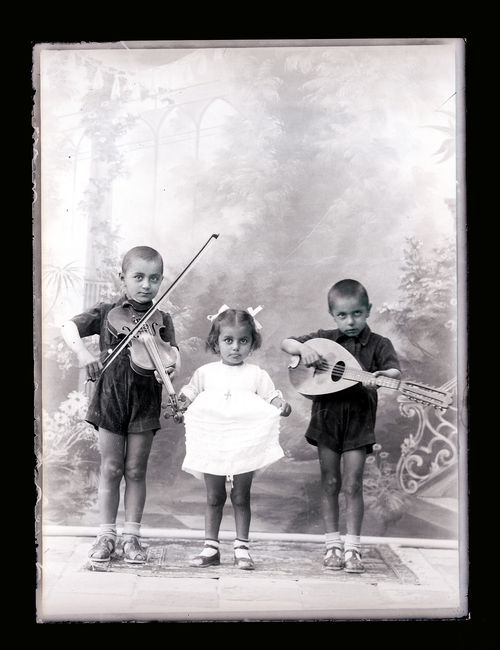 Three children from Esfahan, two boys playing instruments and a younger girl holding out the skirt of a white dress