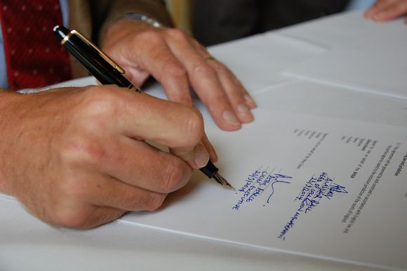 A close up of Alasdair's hand signing the contract in blue ink.