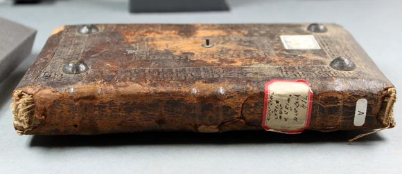 The Or 10721 spine, showing wear and tear where the leather is scuffed and abraded. The damaged endband is visible on the left side of the spine--the book rests horizontally on a table.