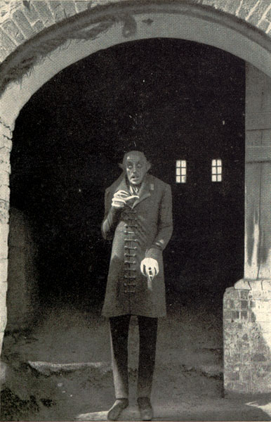 Nosferatu (played by Max Schreck) standing in his castle gateway, from the 1922 film