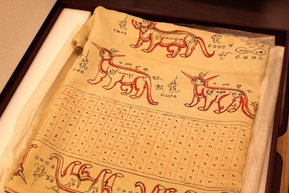 A folded silk textile. The silk is a cream colour. Near the top of the fold there are three animals resembling dogs with pointy ears. Near the bottom is a table with numerous symbols.