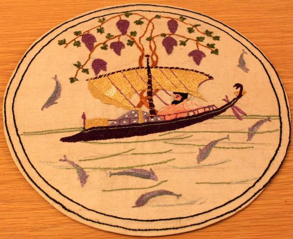 A circular embroidery showing a man resting in a boat, with dolphins swimming around him and above him is a grape tree.