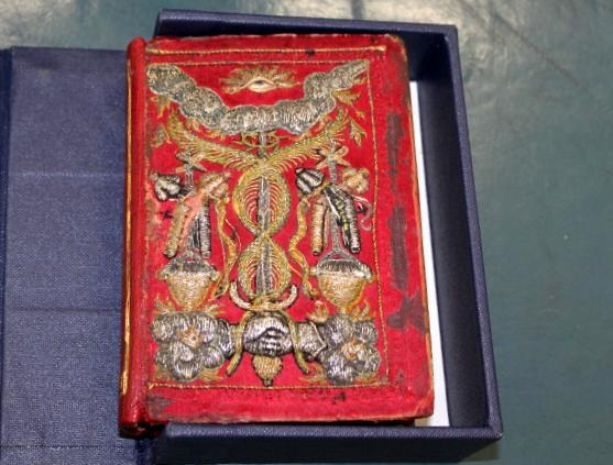 An intricately embroidered book cover. The cover is red, and the embroidery has a three-dimensional quality in mainly silver and gold threads. At the top of the book cover is am embroidered eye, with a cloud below. Twisting threads surround a sword which is held by two hands.