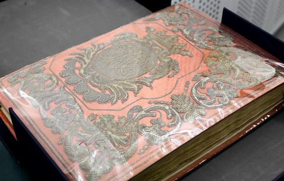 An embroidered book cover on coral-coloured cloth. The embroidery has a three-dimensional quality. At the centre is a crest-like design, with swirling filigree around the edges. The book cover is protected with a plastic covering.