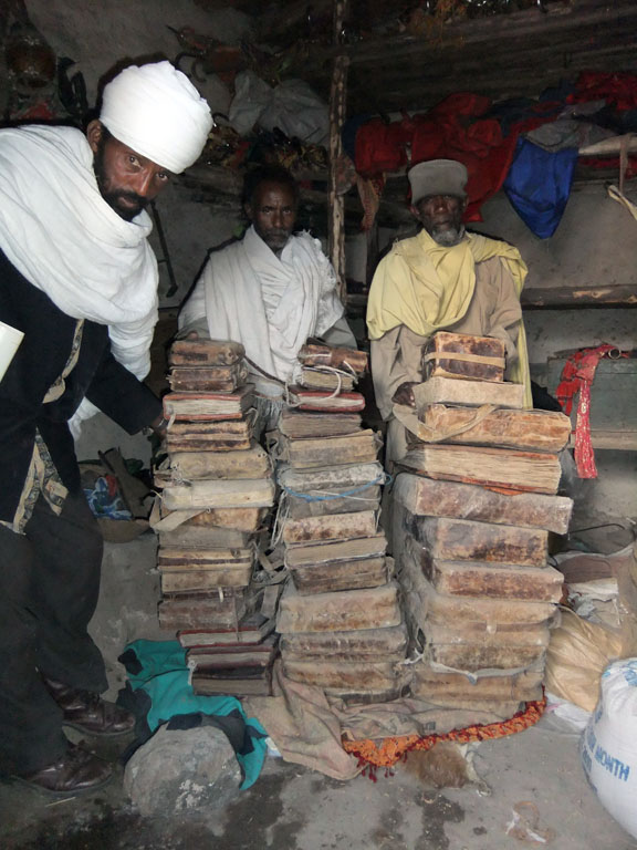 Three men look directly at the camera, they stand next to three large piles of Ethiopian manuscripts.