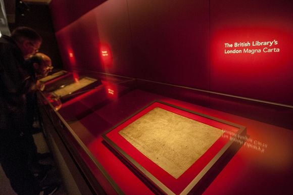 The Magna Carta in its frame sits in a displace case in the exhibition.