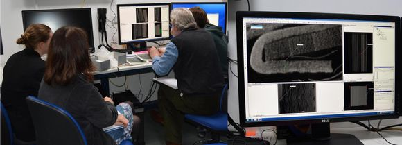 Two images stitched together. Left: Four people sit in office chairs surrounding a desktop computer, looking at the results on the monitor. Right: An image of the computer monitor showing a couple black and white images--results from the scanning.