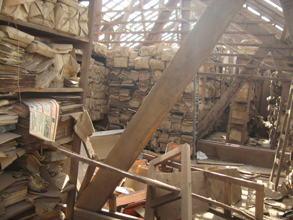 Interior of a wooden building without a roof. Archives are stacked randomly on shelves and on the floor