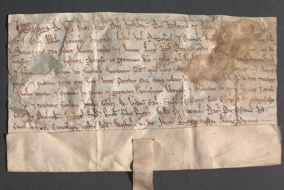A piece of parchment with texts rests on a neutral background. The raking light shows off the folds and undulations of the item.