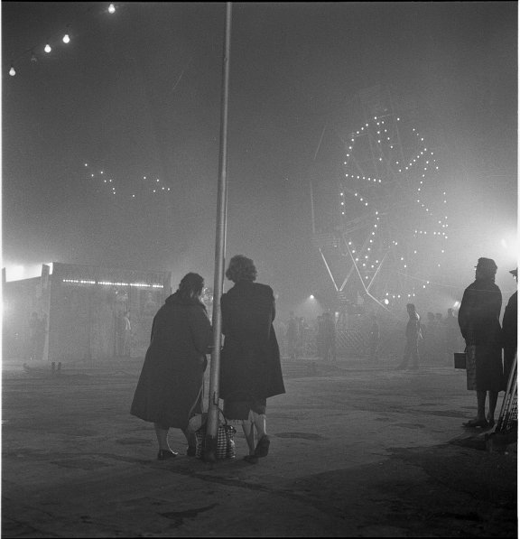 Two women in an amusement park. It looks a misty evening.