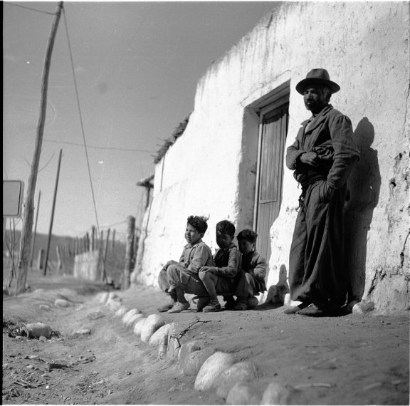 A man stands against the whitewashed exterior wall of a building. Three boys crouch nearby.