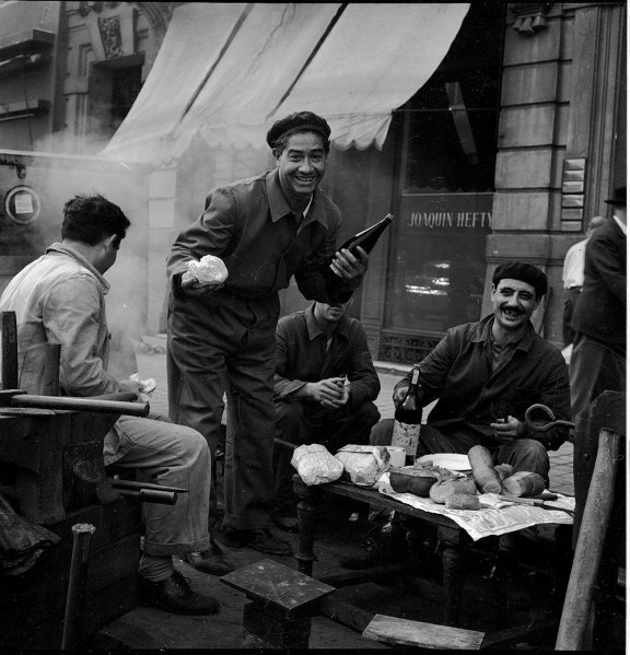 Group of smiling workmen having a meal on a sidewalk. One man holds a bottle of alcohol.