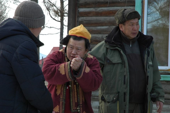 A monk stands in the middle of two team members. He rubs his hands together to keep warm.