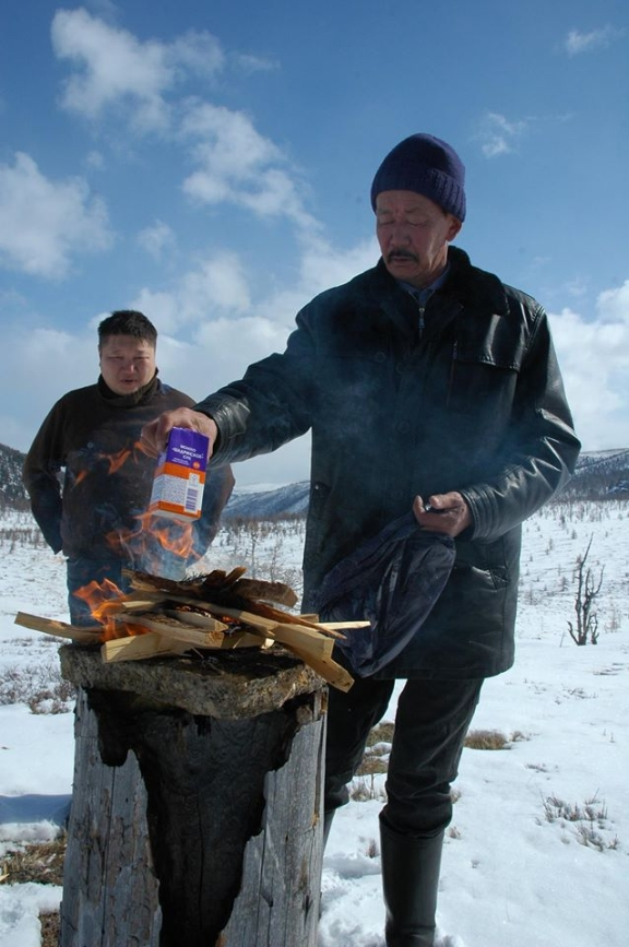 Two team members make a fire in the snowy landscape