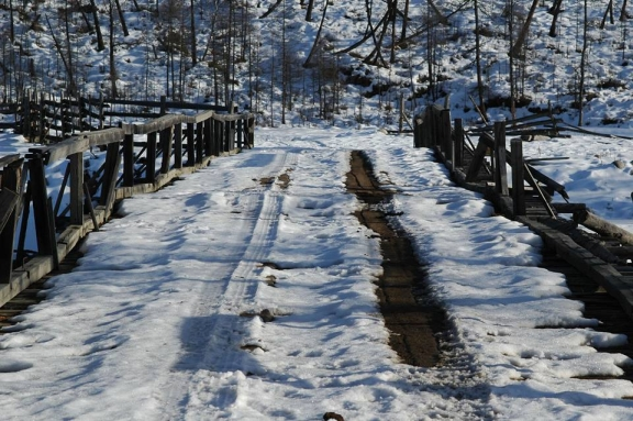 A rickety bridge with tyre tracks through the snow.