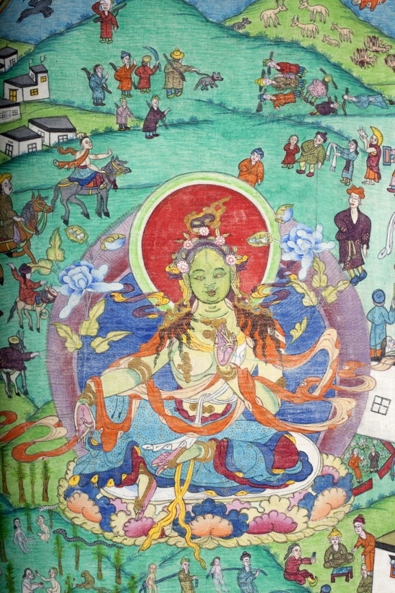 Painting of the diety Green Tara, depictions of daily life can be seen around the central figure.