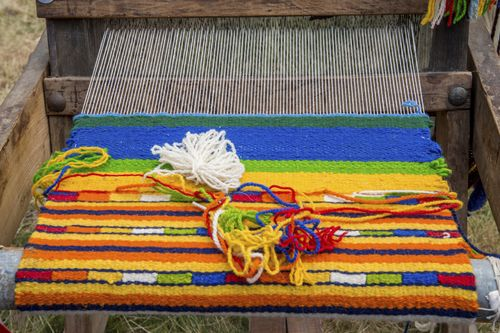 A Bulgarian rug in blue, green, yellow and red being woven on a loom