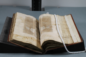 The manuscript sits open on two book supports made of foam.