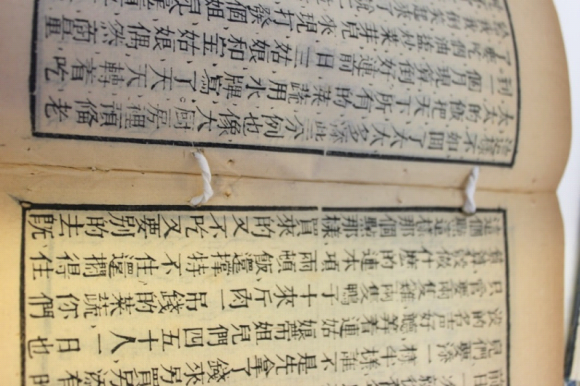 A close up of pages of a book, showing paper twists coming through two holes.