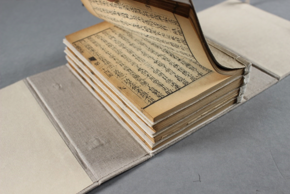 The four fascicules sit stacked on a table, while some of the first pages of the top volumes are lifted open.