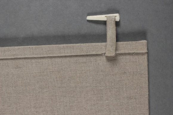 A close up of the case showing the cloth and bone peg.