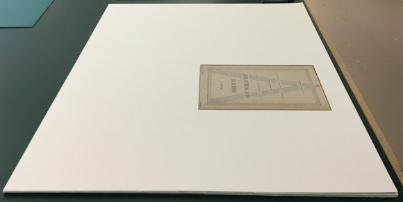The top layer of white board with a cutout where the book's pages show through.