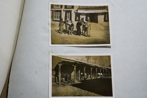 Photograph album. Top photograph shows four men stand next to two horses, bottom photograph shows the stables.,