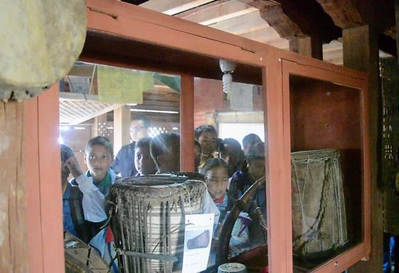 School children look at drums in a glass case.