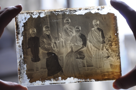 Close up of a glass negative being placed to the light.