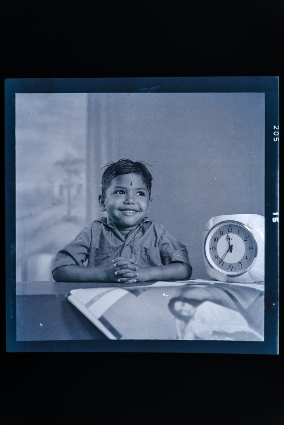 Portrait of a boy sitting next to a clock.