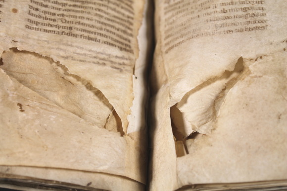 Two large cut marks in the manuscript pages, on opposing sides of the parchment leaves as the book is opened.