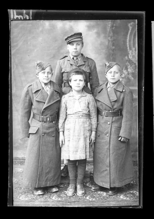 Portrait  photograph of four Polish refugee children wearing uniforms